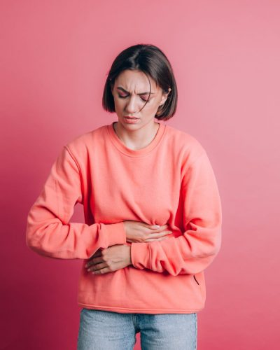woman-wearing-casual-sweater-background-suffering-stomach-ache-with-painful-grimace-feeling-sudden-period-cramps-gynecology-concept (1)